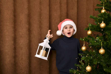 Foto de An enthusiastic child, opened his mouth in surprise, jumped out from behind the Christmas tree with a lantern. - Imagen libre de derechos