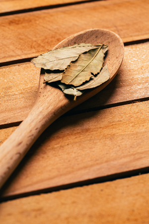 bay leaf in a light wooden spoon close up.