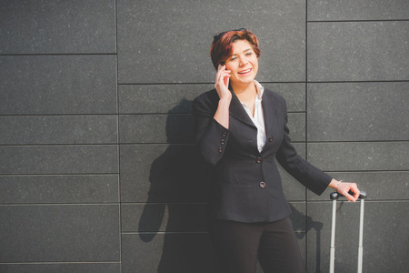 young authentic business woman talks on her smartphone in the financial district for business trip