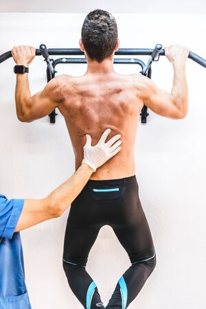 Back of a shirtless patient with a physical therapist in a dominated one. Physiotherapy with protective measures for the Coronavirus pandemic, COVID-19. Osteopathy, therapeutic chiromassage