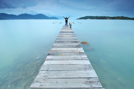 long exposure of man open arms to express victory and freedom at wooden jetty at sea facing island with cloud and sky at twilight .