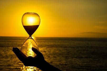 Photo pour Time Concept Hourglass and Sun Setting on the Atlantic Ocean - image libre de droit