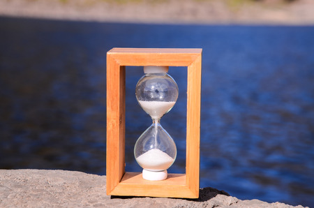 Time Concept White Sand Hourglass on the Volcanic Rocks