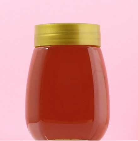 One Full Honey Jar on a Colored  Backgroundの写真素材