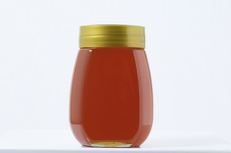 One Full Honey Jar on a White Backgroundの写真素材
