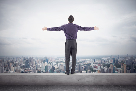 Confident businessman in a purple shirt and trausers standing on the edge of the roof with his hands on the sides in front of the magnificent view of the city.