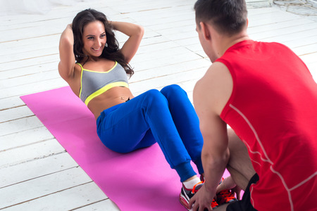 athletic sporty couple friends. Woman doing crunches abdominal exercises on floor in gym with a help of guy concept training exercising workout fitness aerobic.