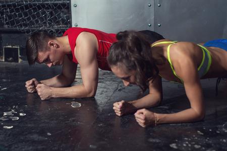 Foto de fit sportive man and woman doing plank core exercise training back and press muscles concept gym sport sportsman crossfit fitness workout strenght power. - Imagen libre de derechos