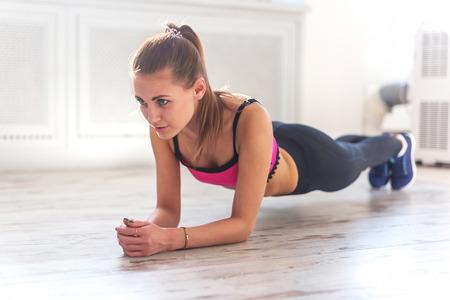 Foto de Slim fitnes young girl with ponytail doing planking exercise indoors at home gymnastics. - Imagen libre de derechos
