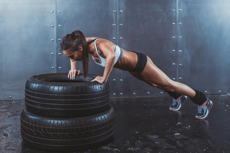 Foto de Sportswoman. Fit sporty woman doing push ups on tire strength power training concept crossfit fitness workout sport and lifestyle - Imagen libre de derechos