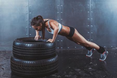 Photo pour Sportswoman. Fit sporty woman doing push ups on tire strength power training concept crossfit fitness workout sport and lifestyle - image libre de droit