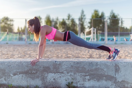Fitness woman doing push ups Outdoor training workout summer evening side view Concept sport healthy lifestyle