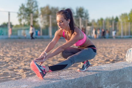 Athletic woman stretching her hamstring, legs exercise training fitness before workout outside on a beach at summer evening with headphones listening music