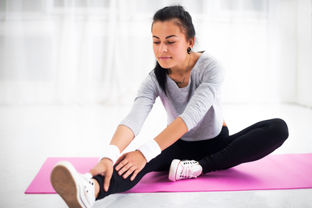 Photo for Fit woman doing aerobics gymnastics stretching exercises her leg and back to warm up at home on yoga mat - Royalty Free Image