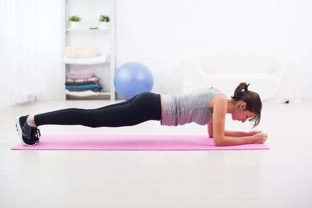 Foto de Fit girl in plank position on mat at home in the living room exercise for back spine and posture Concept pilates fitness sport - Imagen libre de derechos