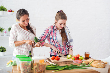Two girls friends preparing dinner in a kitchen concept cooking, culinary, healthy lifestyle