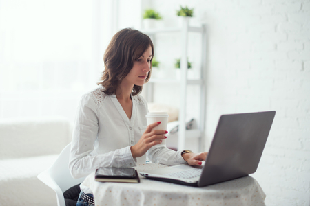 Photo pour young business woman working at desk typing on a laptop in office and drinking coffee. - image libre de droit