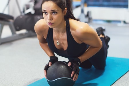 Foto de Fit woman exercising with medicine ball workout out arms Exercise training triceps and biceps doing push ups. - Imagen libre de derechos