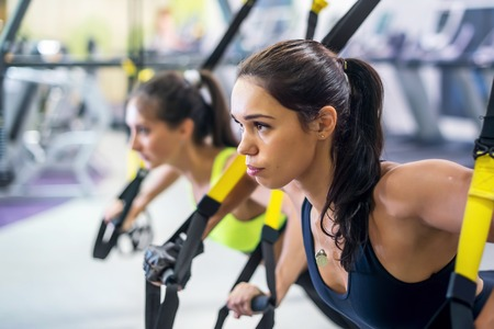 Foto de Fitness trx suspension straps training exercises women doing push-ups, working with own weith at gym - Imagen libre de derechos