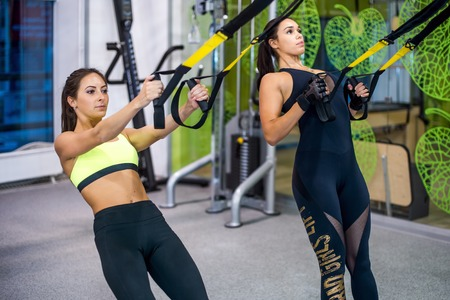 Woman exercising with suspension straps in fitness club or gym