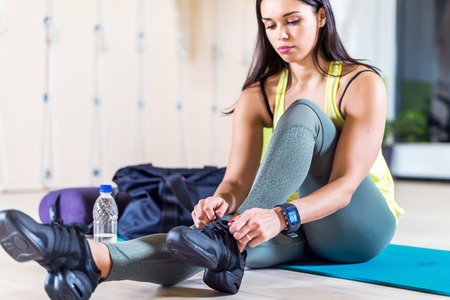 Fit sporty young woman lacing trainers shoes at fitness club