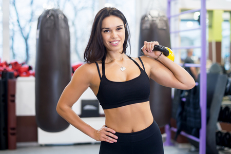 Photo pour Fitness woman doing shoulder press swing exercise with a kettlebell lifting heavy weight smilling and looking at camera. - image libre de droit
