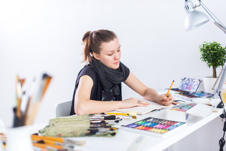 Photo pour Young female artist drawing sketch using sketchbook with pencil at her workplace in studio. Side view portrait of inspired painter - image libre de droit
