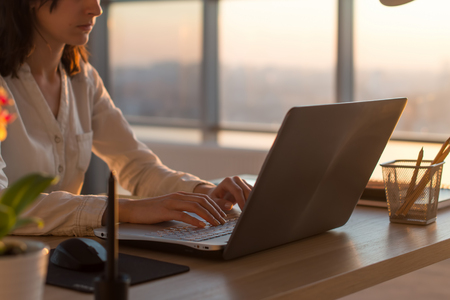 Photo pour Side view photo of a female programmer using laptop, working, typing, surfing the internet at workplace - image libre de droit