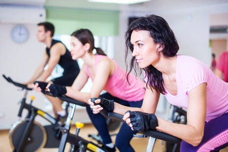 Photo pour Group training people biking in the gym, exercising legs doing cardio workout cycling bikes. - image libre de droit