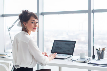 Photo for Attractive businesswoman working at office using pc, searching and studying business ideas on a laptop screen on-line - Royalty Free Image