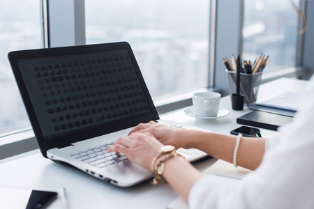 Photo for Side view picture of female hands typing, using pc in a light office. Designer working at workplace, searching new ideas - Royalty Free Image