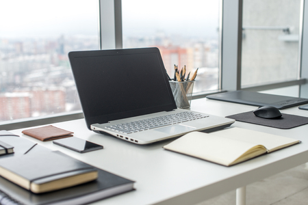 Photo for Workplace with notebook laptop Comfortable work table in office with windows and city view - Royalty Free Image