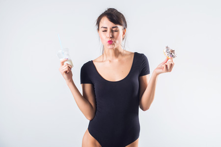 Young brunette model with cocktail and donut studio shot on white background, not isolated.