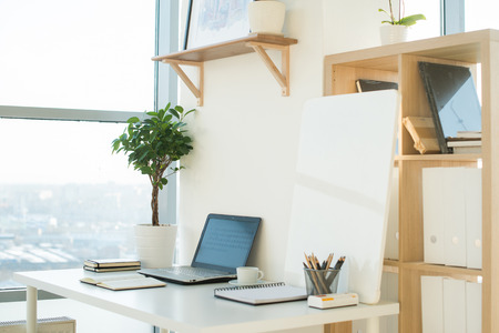 Photo for Side view picture of studio workplace with blank notebook, laptop. Designer comfortable work table, home office - Royalty Free Image
