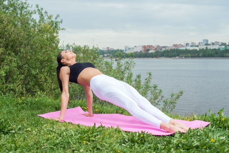 Fit woman stretching body in upward plank pose doing reverse planking exercise on outdoor grass park