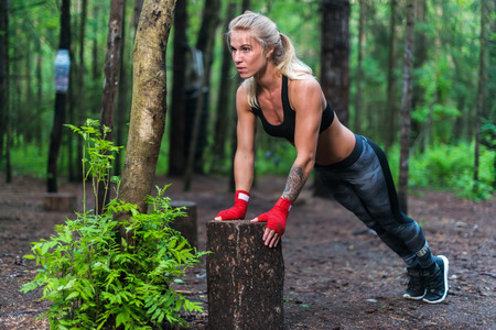 Foto de Muscular woman doing push-ups at park street work out - Imagen libre de derechos