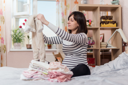Pregnant woman holding and looking at babys clothes