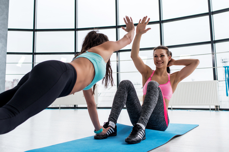 Photo for Fit smiling young woman giving high five to her personal trainer while doing abs workout on a mat in the gym - Royalty Free Image