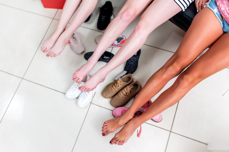 Photo pour Cropped image of three young women spreading out their long barefoot legs relaxing after choosing shoes in shopping center - image libre de droit