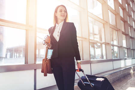 Foto de Pretty smiling female flight attendant carrying baggage going to airplane in the airport - Imagen libre de derechos