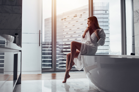 Back view of young woman wearing white bathrobe standing in bathroom looking out the window with bathtub in foregroundの写真素材