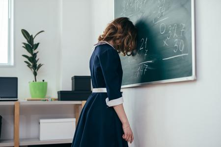 Photo pour Sad schoolgirl standing in front of blackboard. - image libre de droit