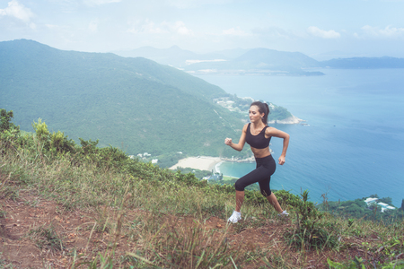 Foto de Slender young female athlete doing cardio exercise going up the mountain with sea in background. - Imagen libre de derechos