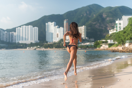 Photo pour Back view of fit slim girl running barefoot on seashore wearing bikini. Young woman doing cardio exercise beach lit in sunshine and city mountains in background. - image libre de droit