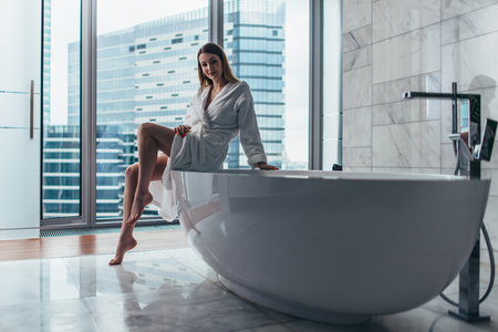 Photo for Back view of young woman wearing white bathrobe standing in bathroom looking out the window with bathtub in foreground - Royalty Free Image