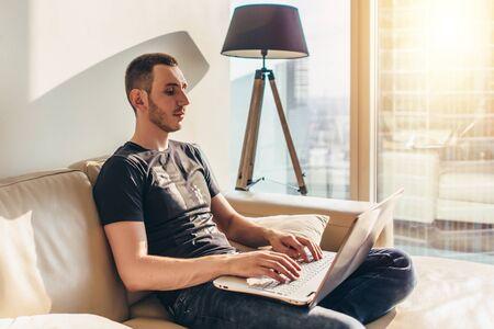 Photo pour Young man using laptop while sitting on a sofa - image libre de droit