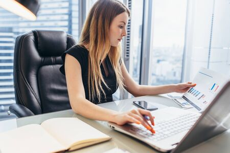 Photo pour Female director working in office sitting at desk analyzing business statistics holding diagrams and charts using laptop - image libre de droit
