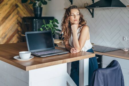 Photo for Pensive woman in the kitchen at the table with a laptop - Royalty Free Image