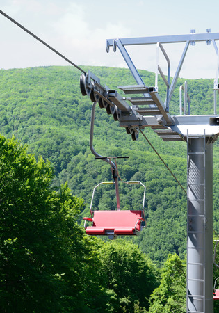 Pole and empty chairlift going over trees in the summer.