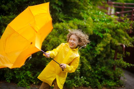 Foto de The boy in a bright yellow raincoat with effort holds an umbrella from wind. Strong wind pulls out a yellow umbrella from his hands. Wind has disheveled hair, drops of a rain drip to him on the head. - Imagen libre de derechos